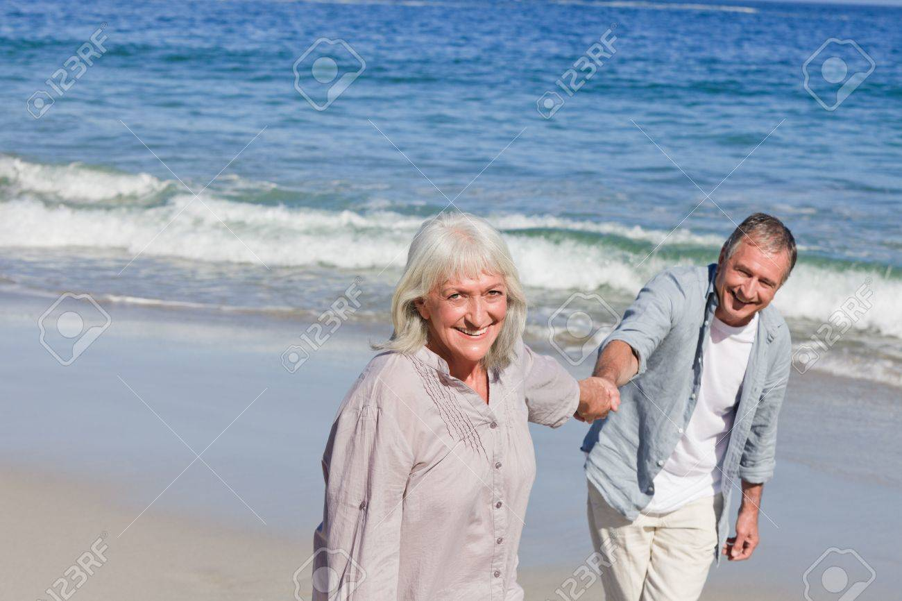 Elderly couple walking on the beach Stock Photo - 10197399