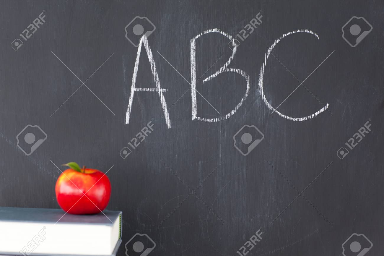 Stack of books with a red apple and a blackboard with