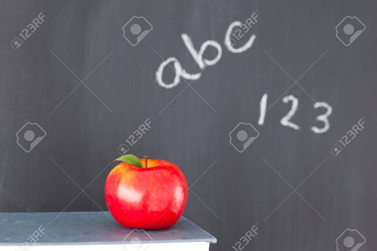 Stack of books with a red apple and a blackboard with figures and letters written on it Stock Photo - 10206708