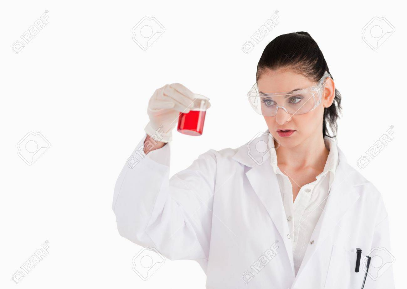 Dark-haired scientist with safety glasses looking at a red beaker in a lab Stock Photo - 10194070