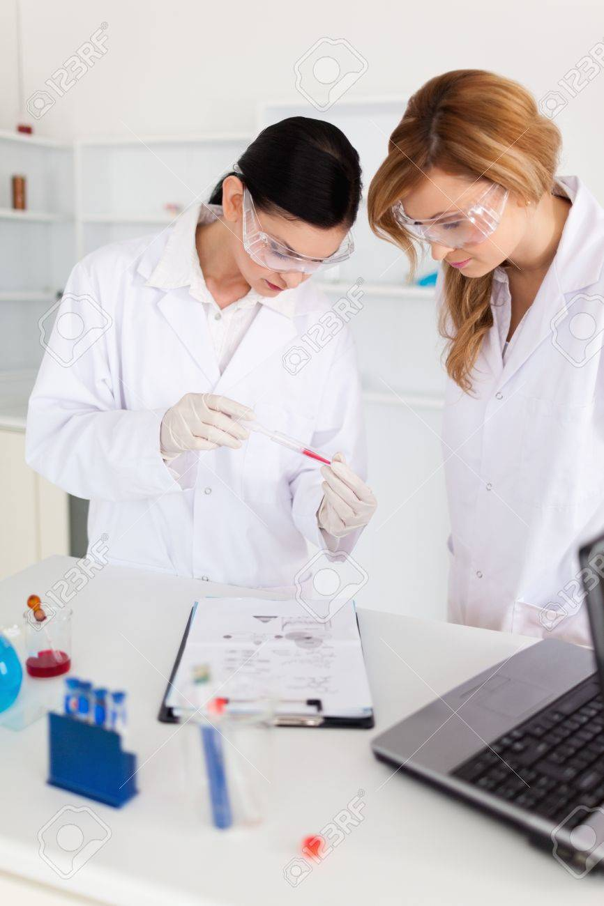 Two scientists observing a test tube in a lab Stock Photo - 10205954