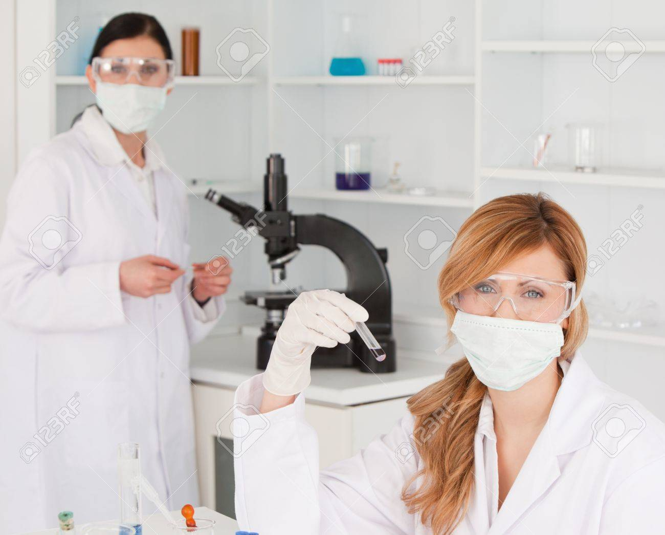 Blond-haired and dark-haired scientists carrying out an experiment in a lab Stock Photo - 10197555