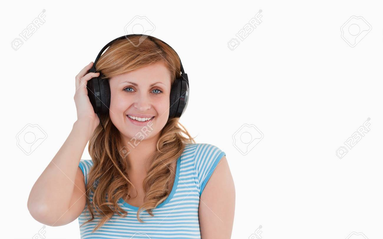 Isolated blond-haired woman listening to music standing on a white background Stock Photo - 10194276