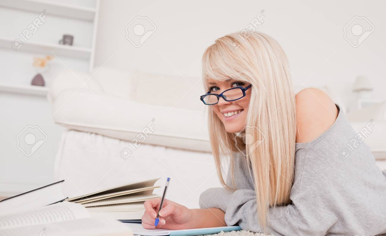 Smiling blonde woman studying while lying on a carpet in the living room Stock Photo - 10197903