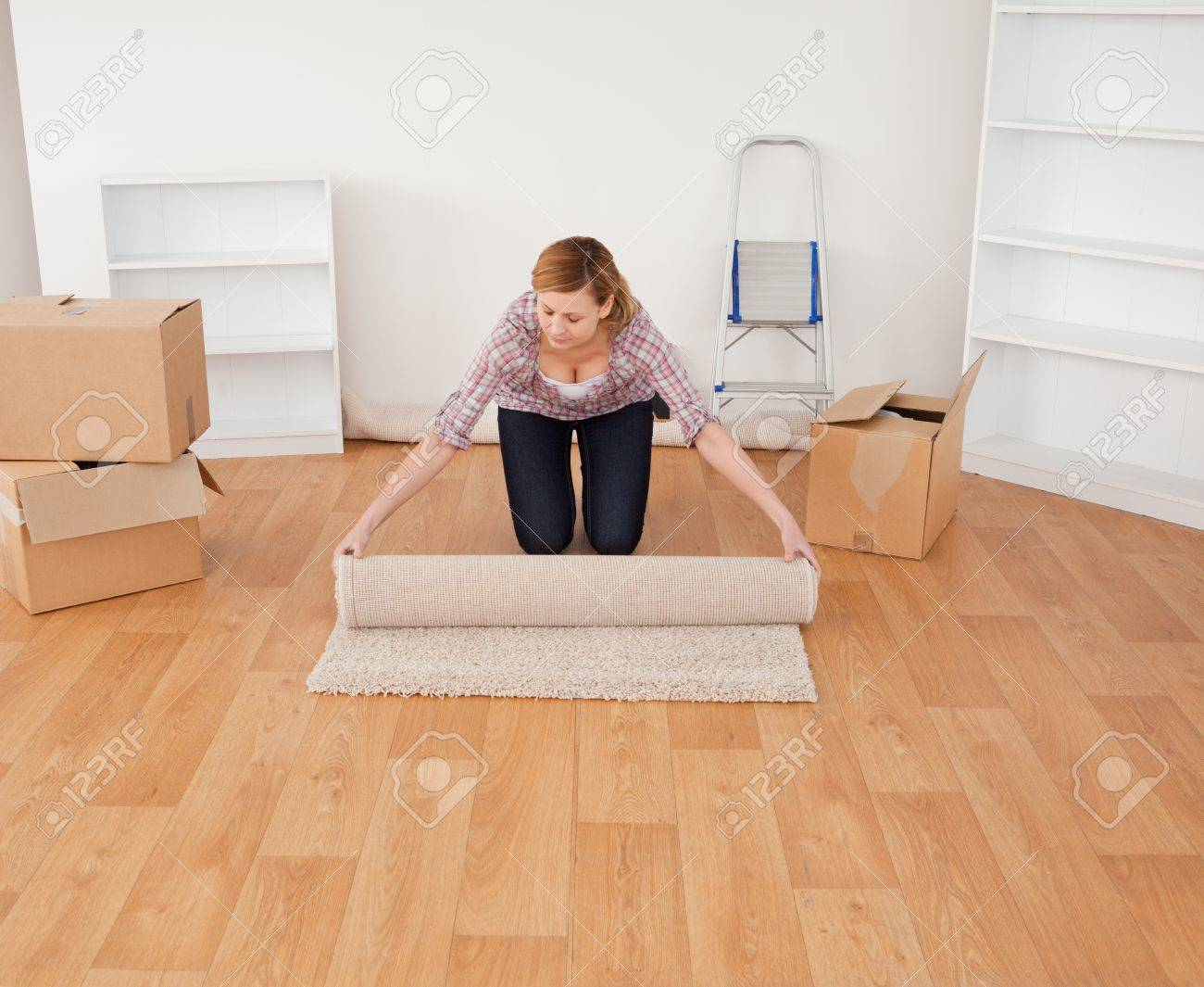 Blond-haired woman rolling up a carpet to prepare to move house Stock Photo - 10205880