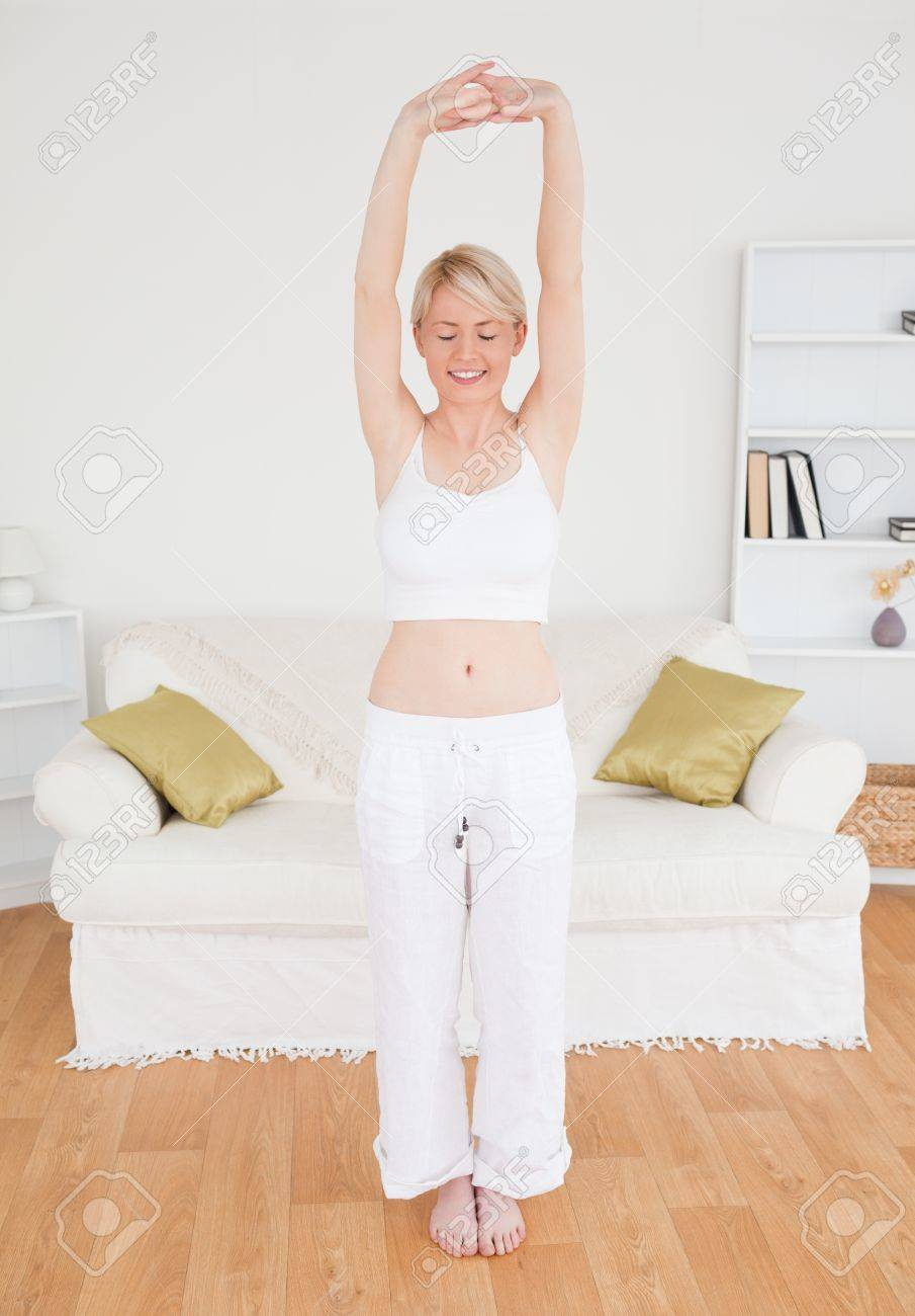 Beautiful woman stretching in the living room in her appartment Stock Photo - 10197934