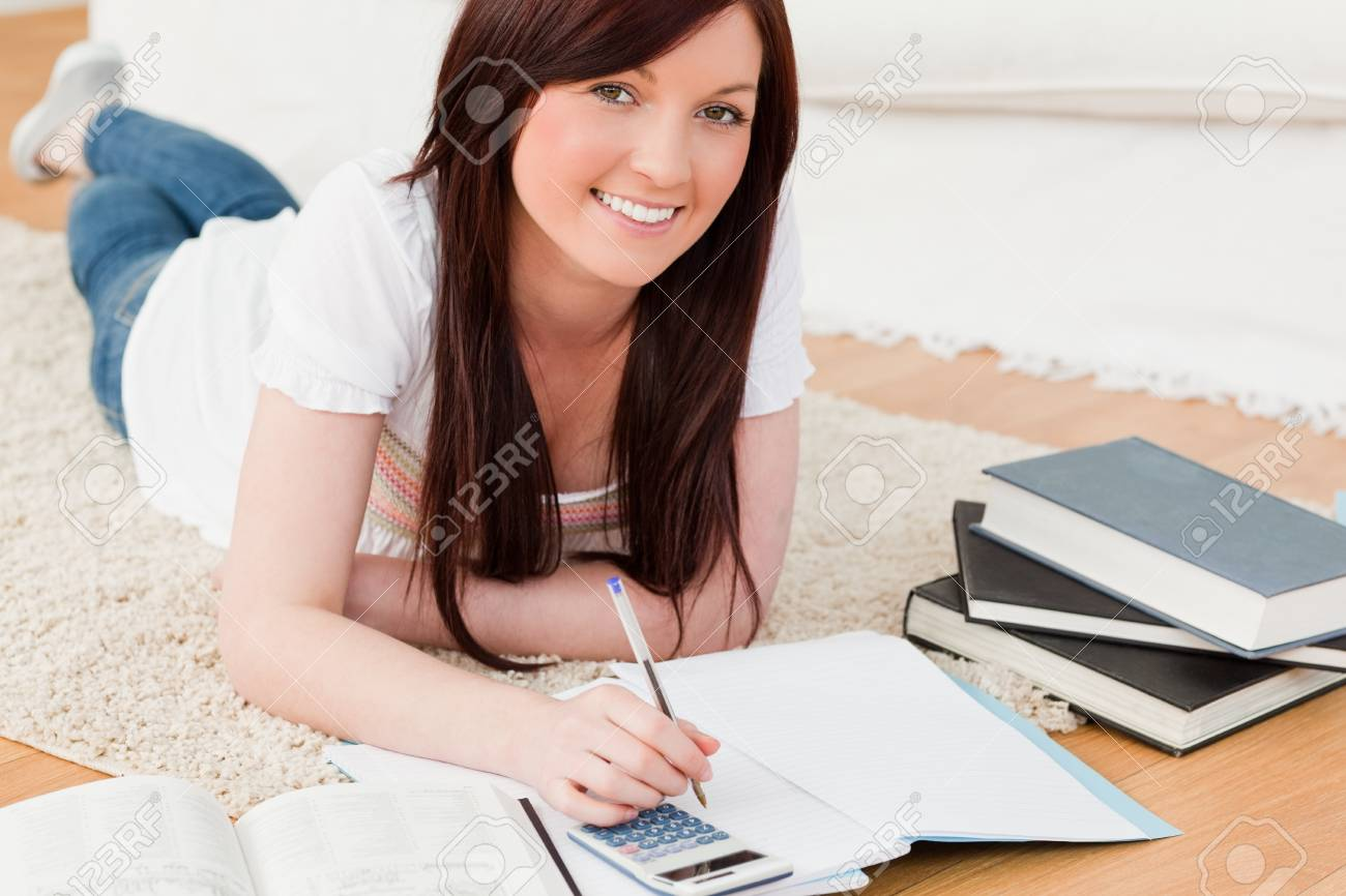 Beautiful red-haired female studying for while lying on a carpet in the living room Stock Photo - 10205903