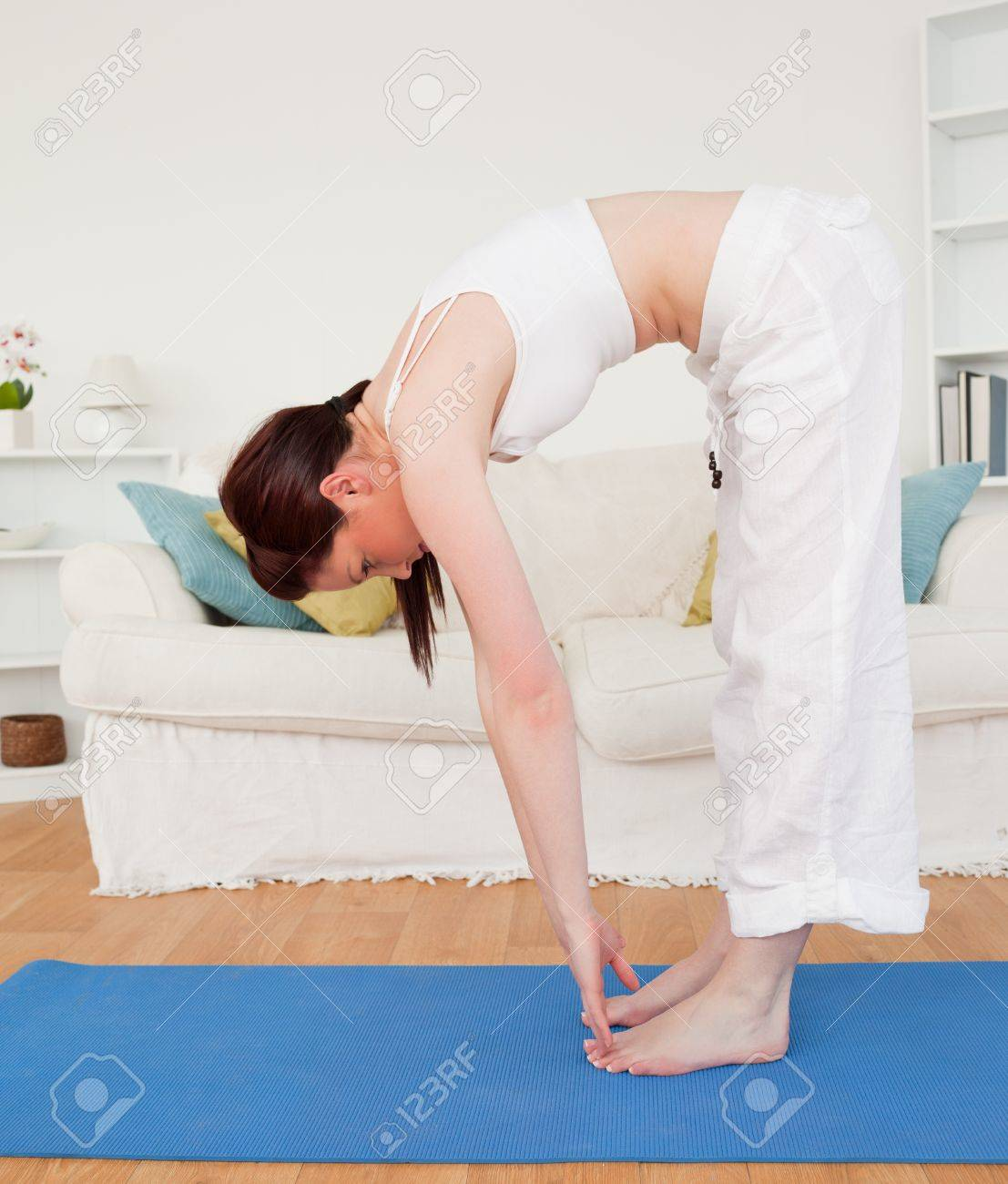 Attractive red-haired female stretching in the living room in her appartment Stock Photo - 10198417
