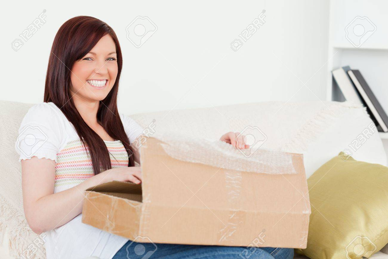 Beautiful red-haired woman opening a carboard box while sitting on a sofa in the living room Stock Photo - 10198420