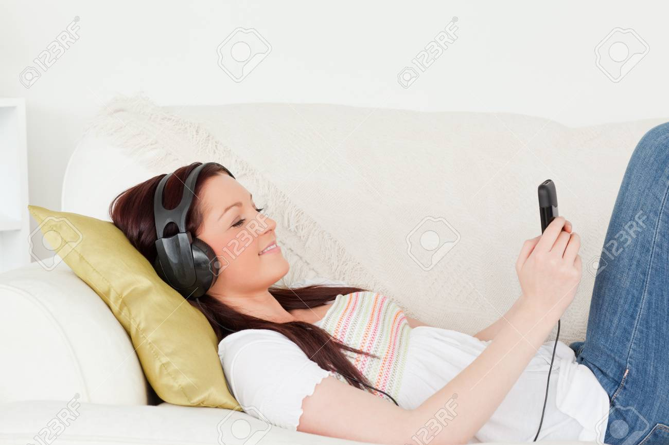 Attractive red-haired woman listening to music with headphones while lying on a sofa in the living room Stock Photo - 10205864