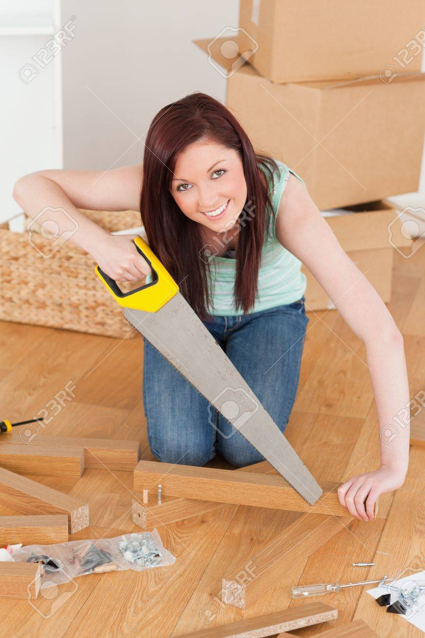 Good looking red-haired woman using a saw for diy at home Stock Photo - 10206685