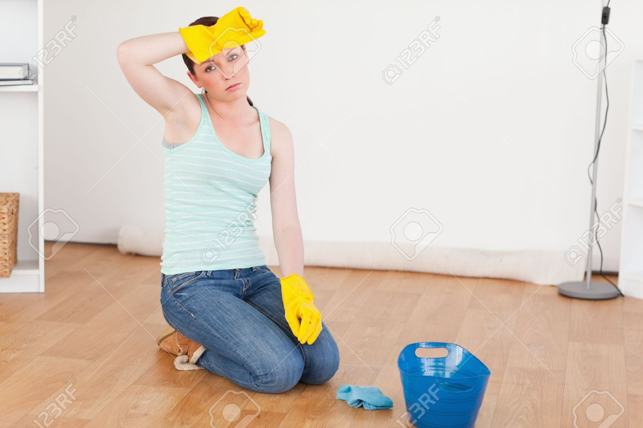 Cute red-haired woman having a break while cleaning the floor at home Stock Photo - 10205941