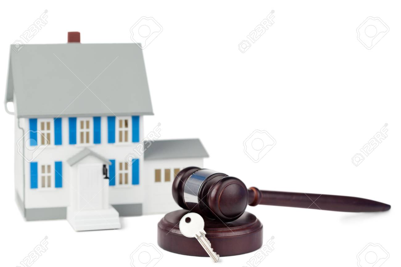 Grey toy house model with a key and a brown gavel against a white background Stock Photo - 10193461
