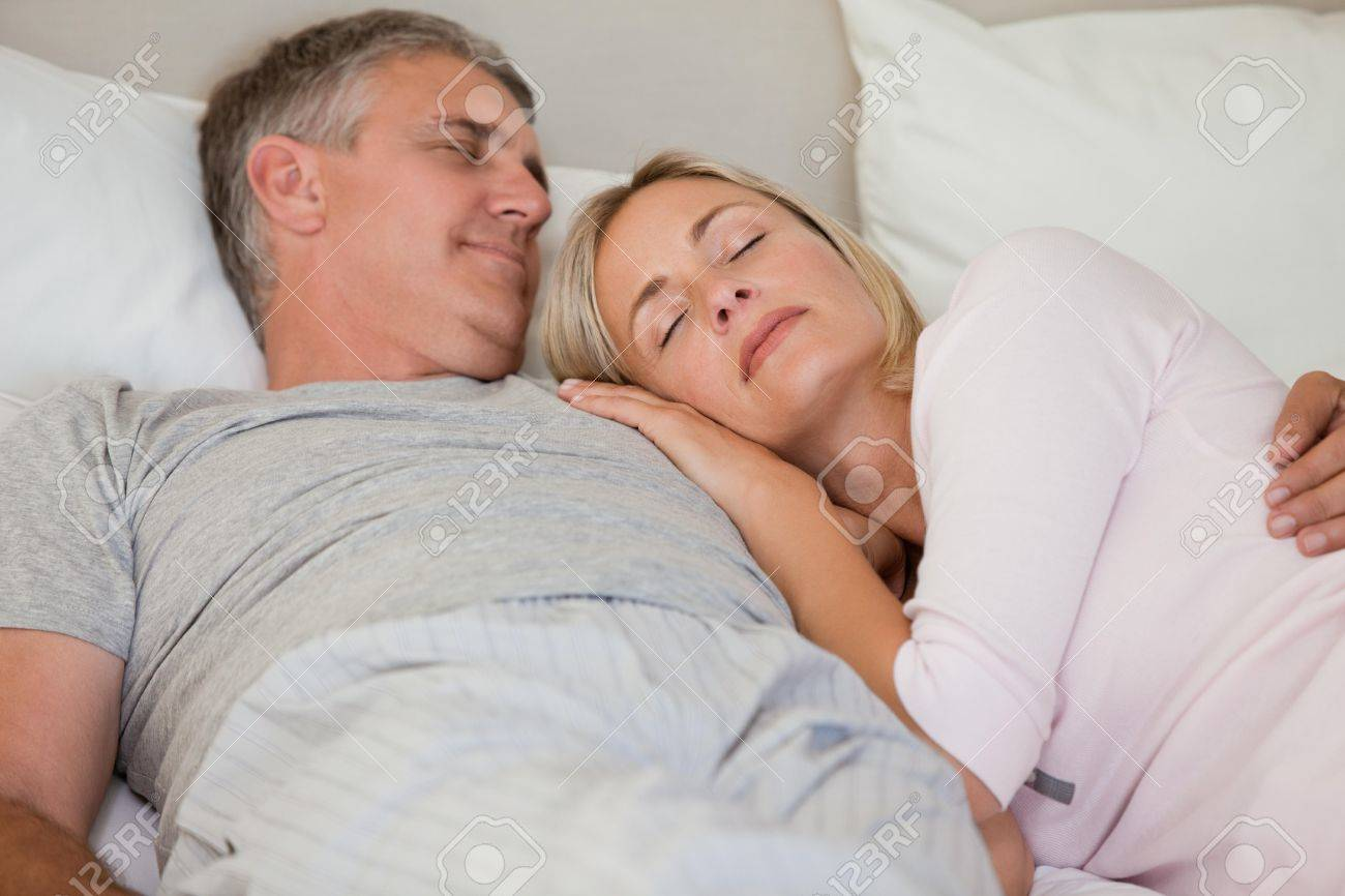 Beautiful couple sleeping on their bed Stock Photo - 10196064