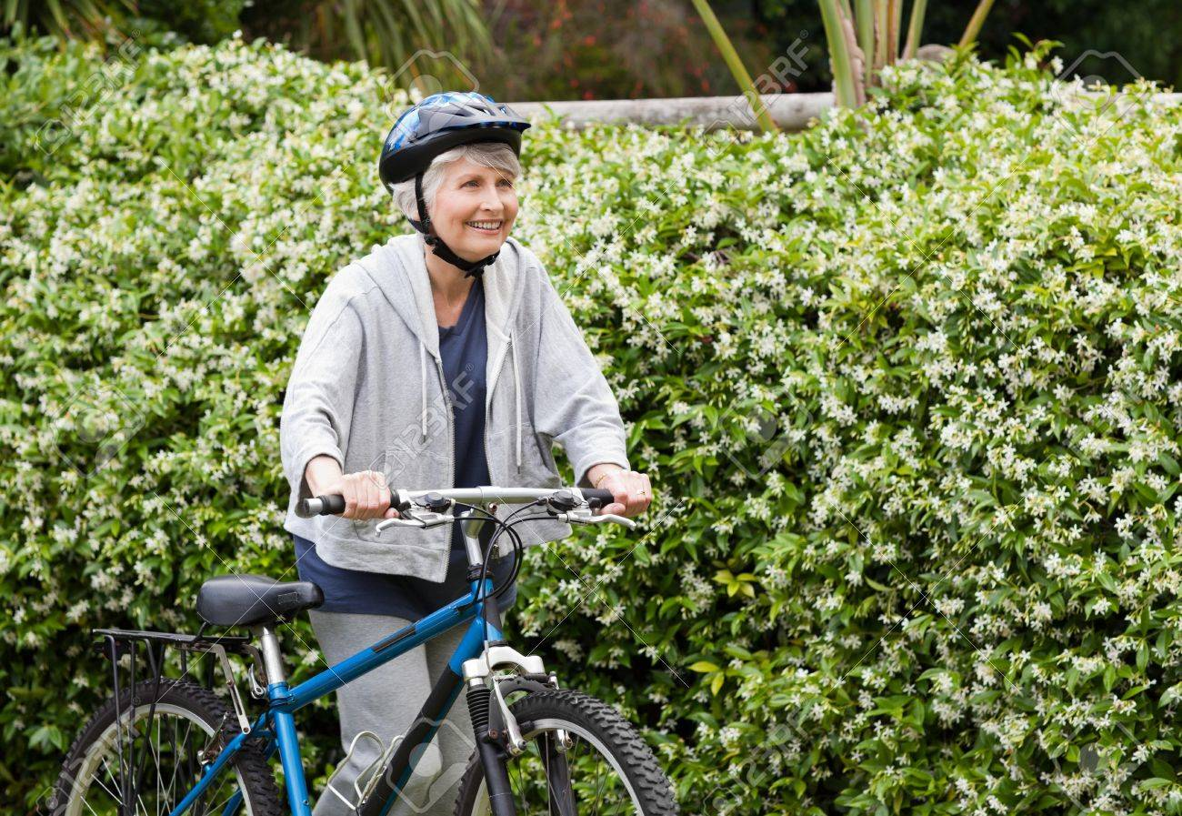 Mature woman walking with her mountain bike Stock Photo - 10199010