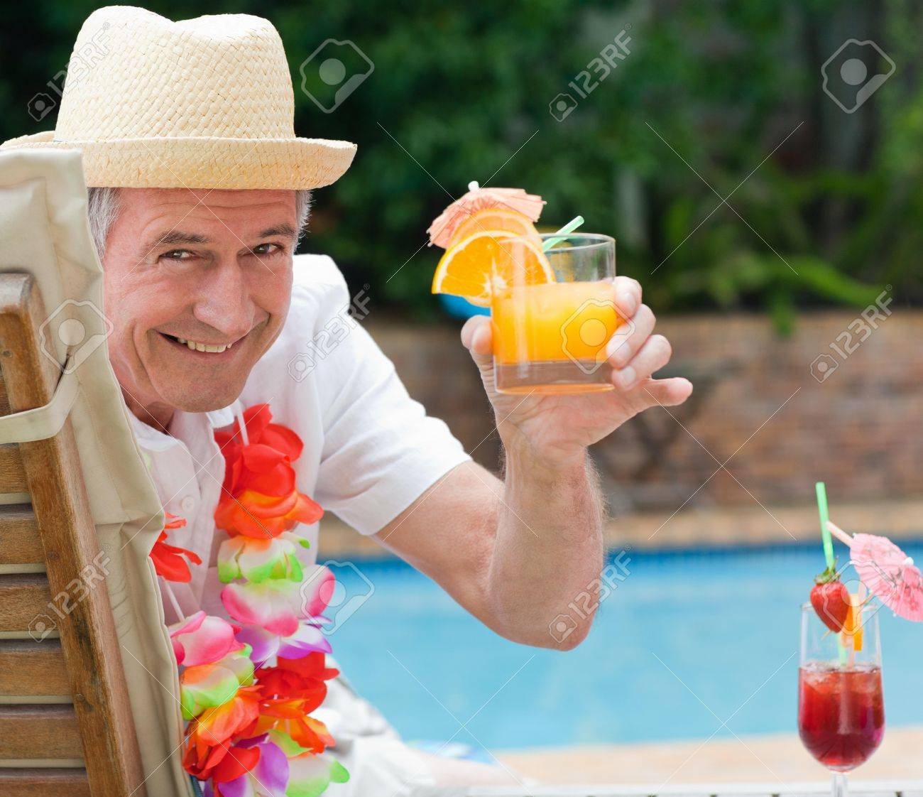 Mature man drinking a cocktail  beside the swimming pool Stock Photo - 10194660