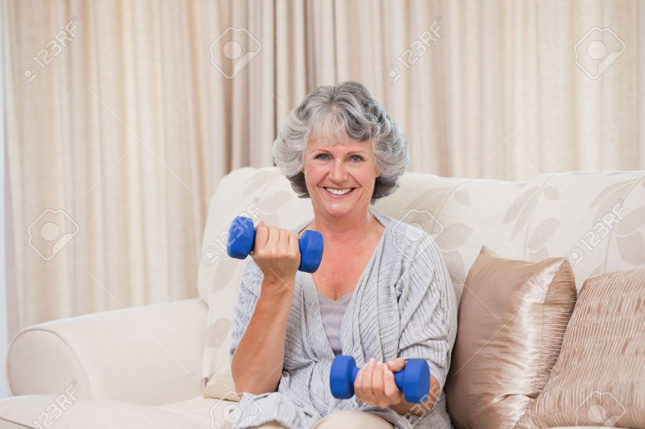 Woman doing her exercises on her sofa Stock Photo - 10197669