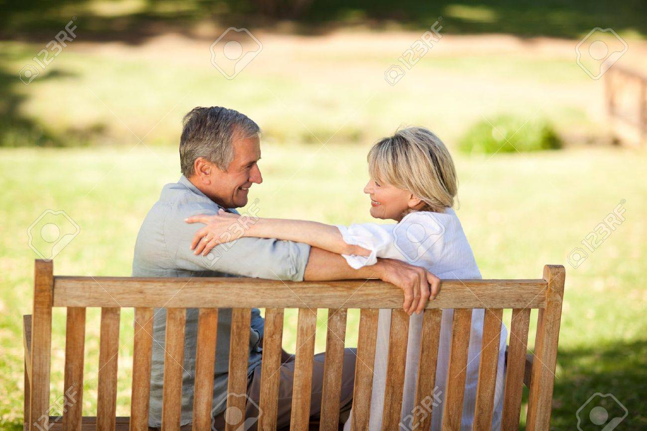 Happy retired couple sitting on the bench Stock Photo - 10216686