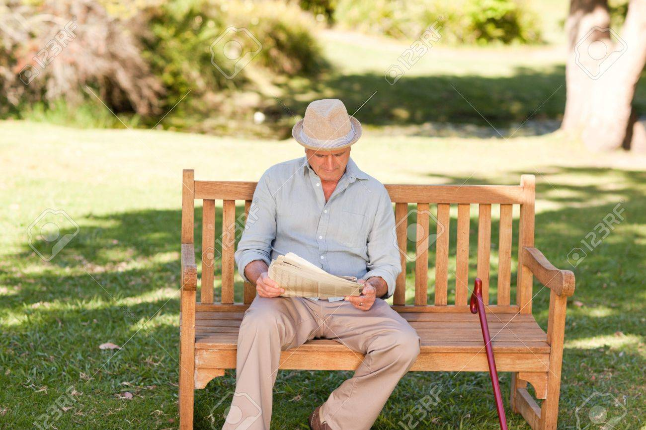 Retired man reading his newspaper on the bench - 10219096