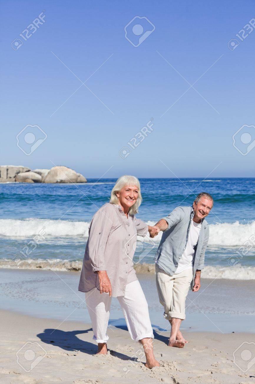 Elderly couple walking on the beach Stock Photo - 10218888