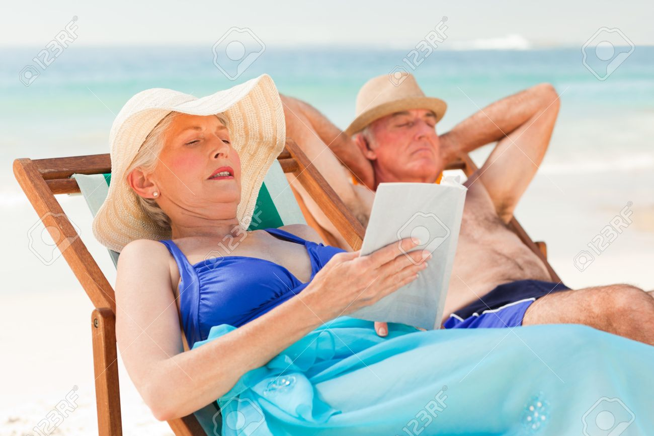 Woman reading a book while her husband is sleeping at the beach Stock Photo - 10214087