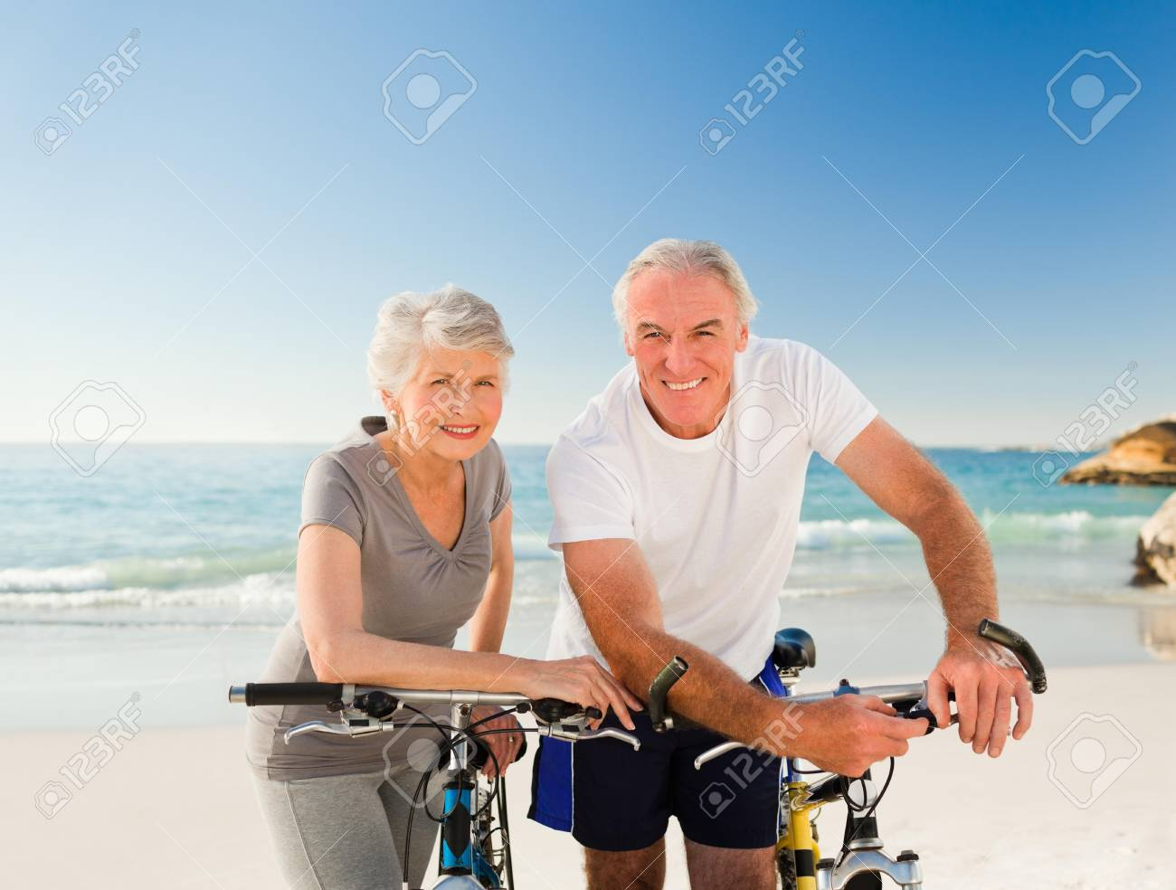 Retired couple with their bikes on the beach Stock Photo - 10214651