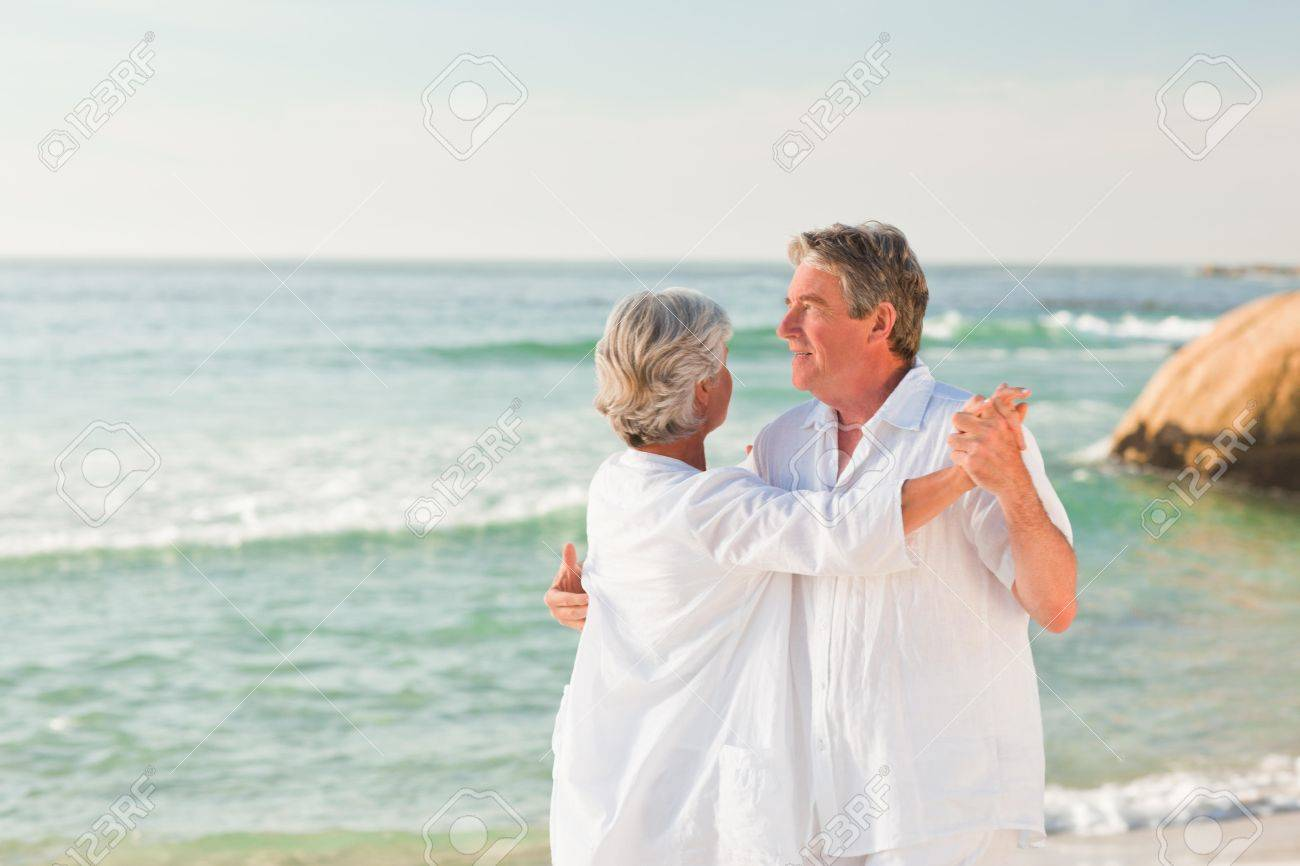 Elderly couple dancing on the beach Stock Photo - 10207617