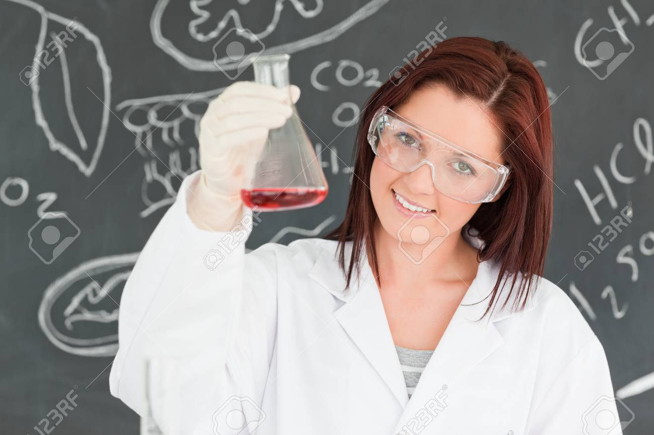Close up of a cute scientist showing a conical flask in a classroom Stock Photo - 10220564