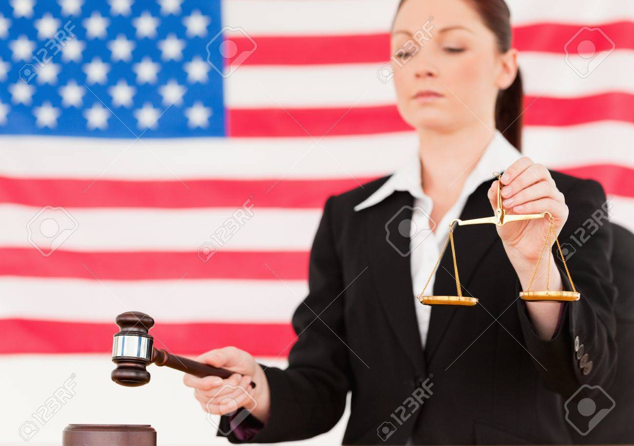 Close up of a young judge knocking a gavel and holding scales of justice with an American flag in the background Stock Photo - 10219410