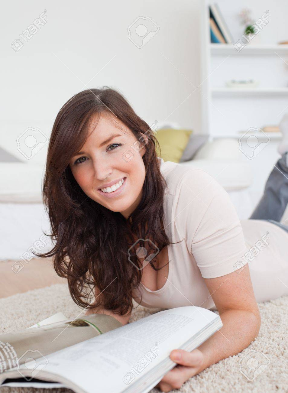 Beautiful woman reading a magazine while lying on a carpet in the living room Stock Photo - 10216237