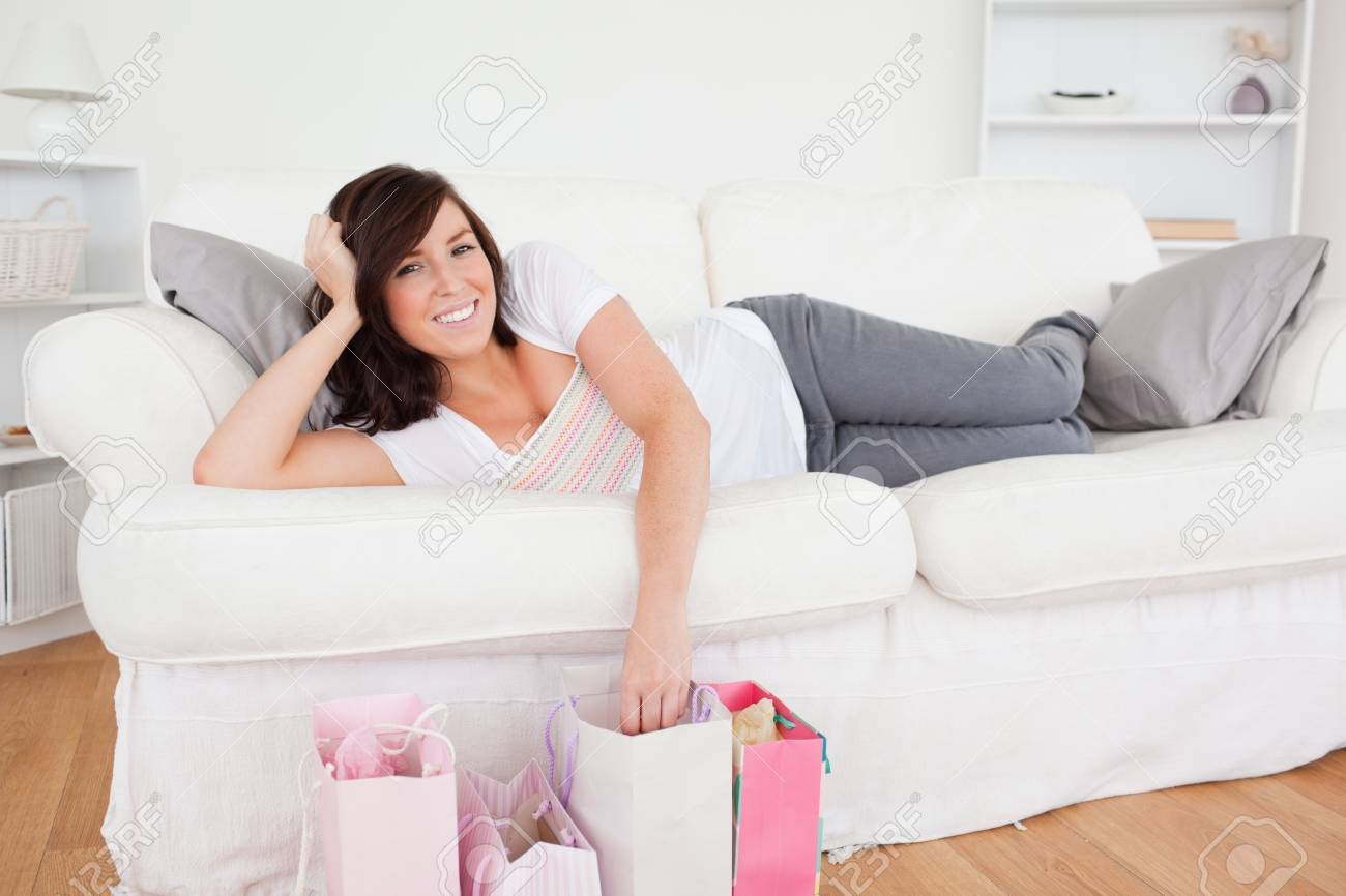 Young gorgeous female posing with her shopping bags while lying on a sofa in the living room Stock Photo - 10219265
