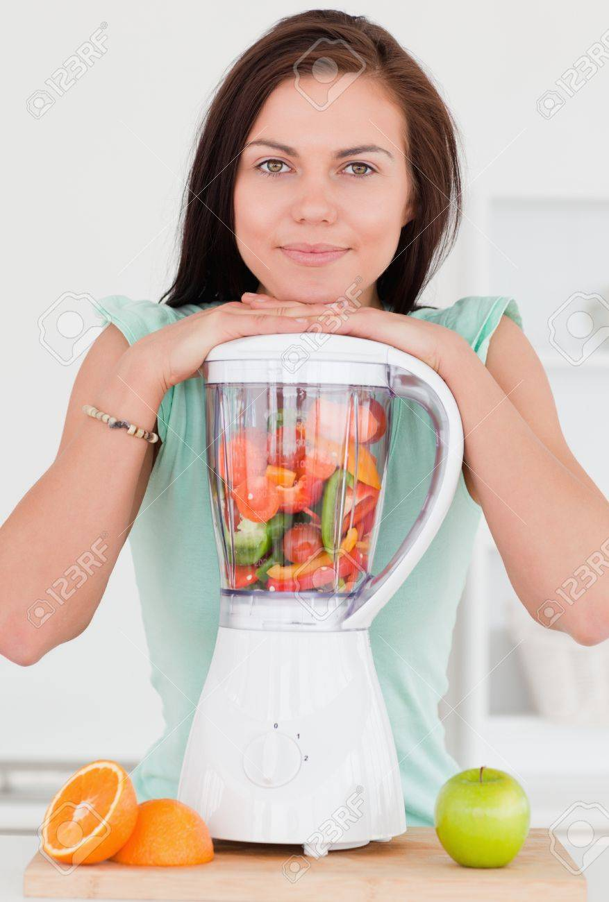 Smiling dark-haired woman posing with a blender in her kitchen Stock Photo - 10220962