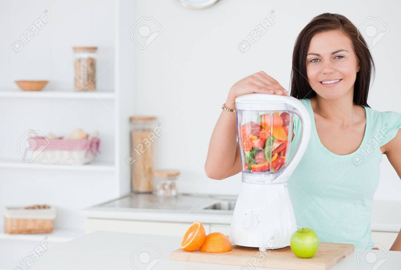 Dark-haired woman posing with a blender Stock Photo - 10221087