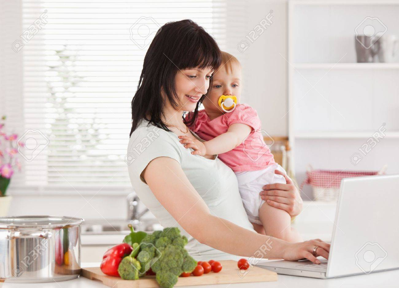 Good looking woman holding her baby in her arms while standing in the kitchen Stock Photo - 10220905