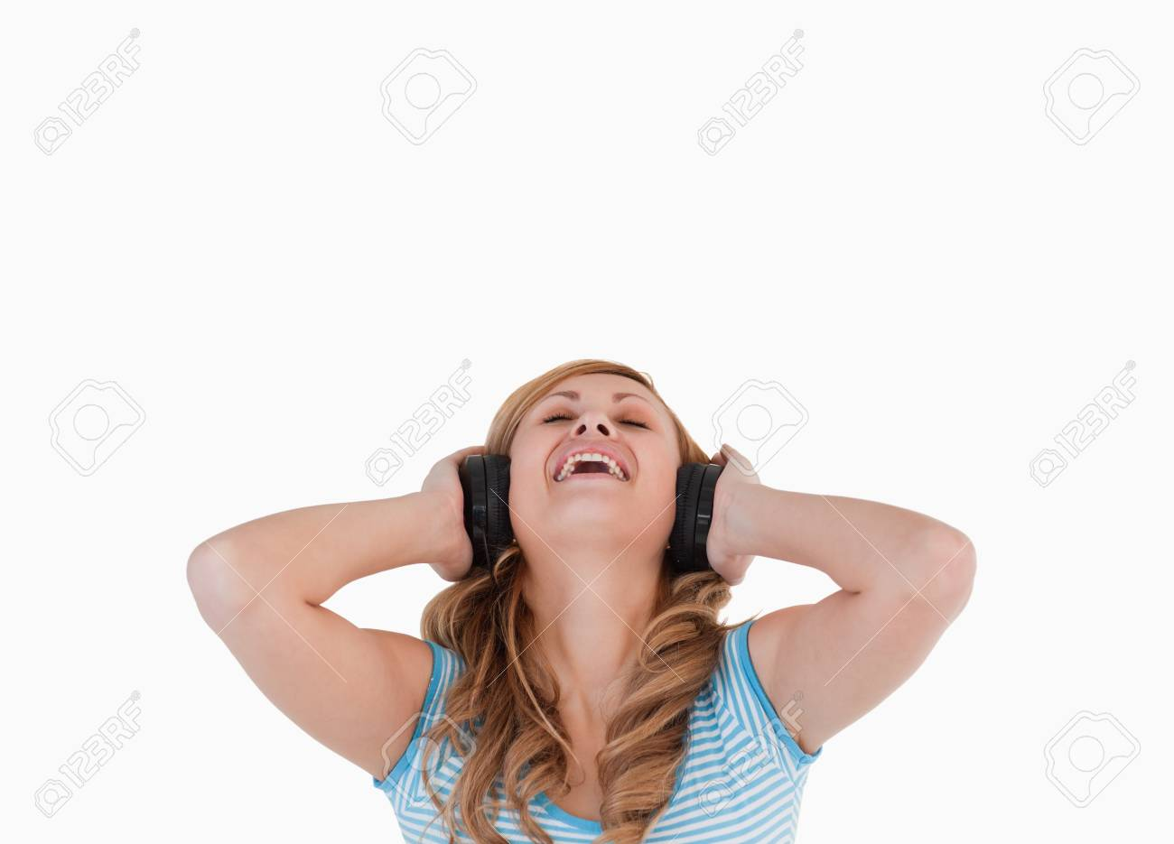 Attractive blond-haired woman happy while listening to music standing on a white background Stock Photo - 10191708