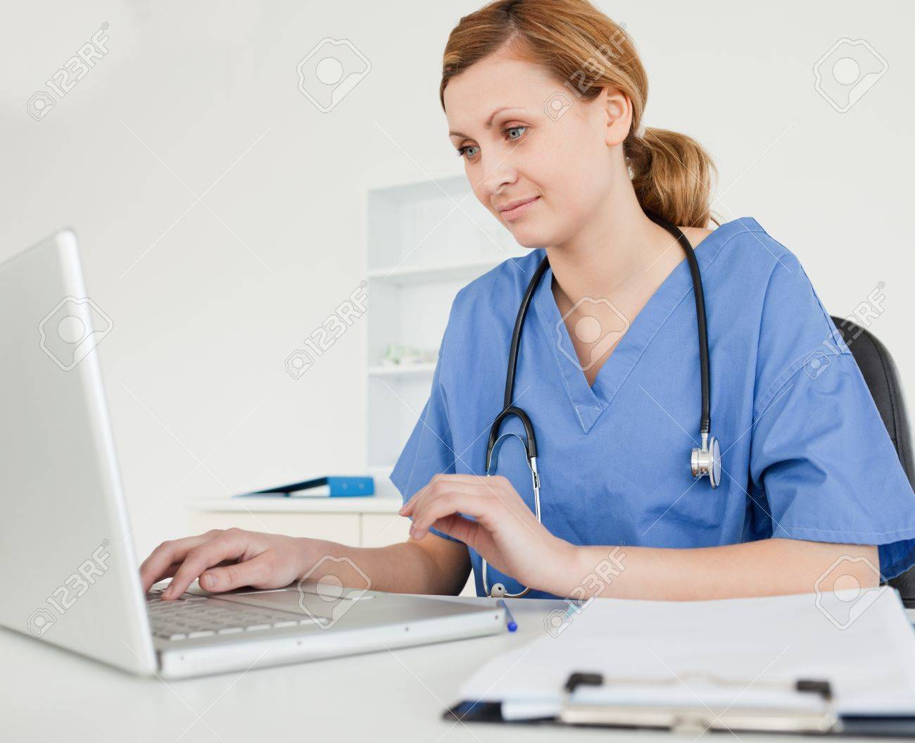 Cute female doctor working on her laptop in her surgery Stock Photo - 10069453