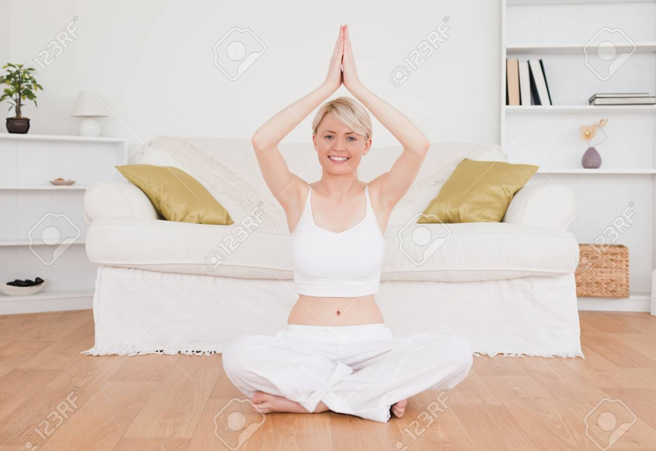 Happy blond-haired woman practicing yoga at home Stock Photo - 10191690