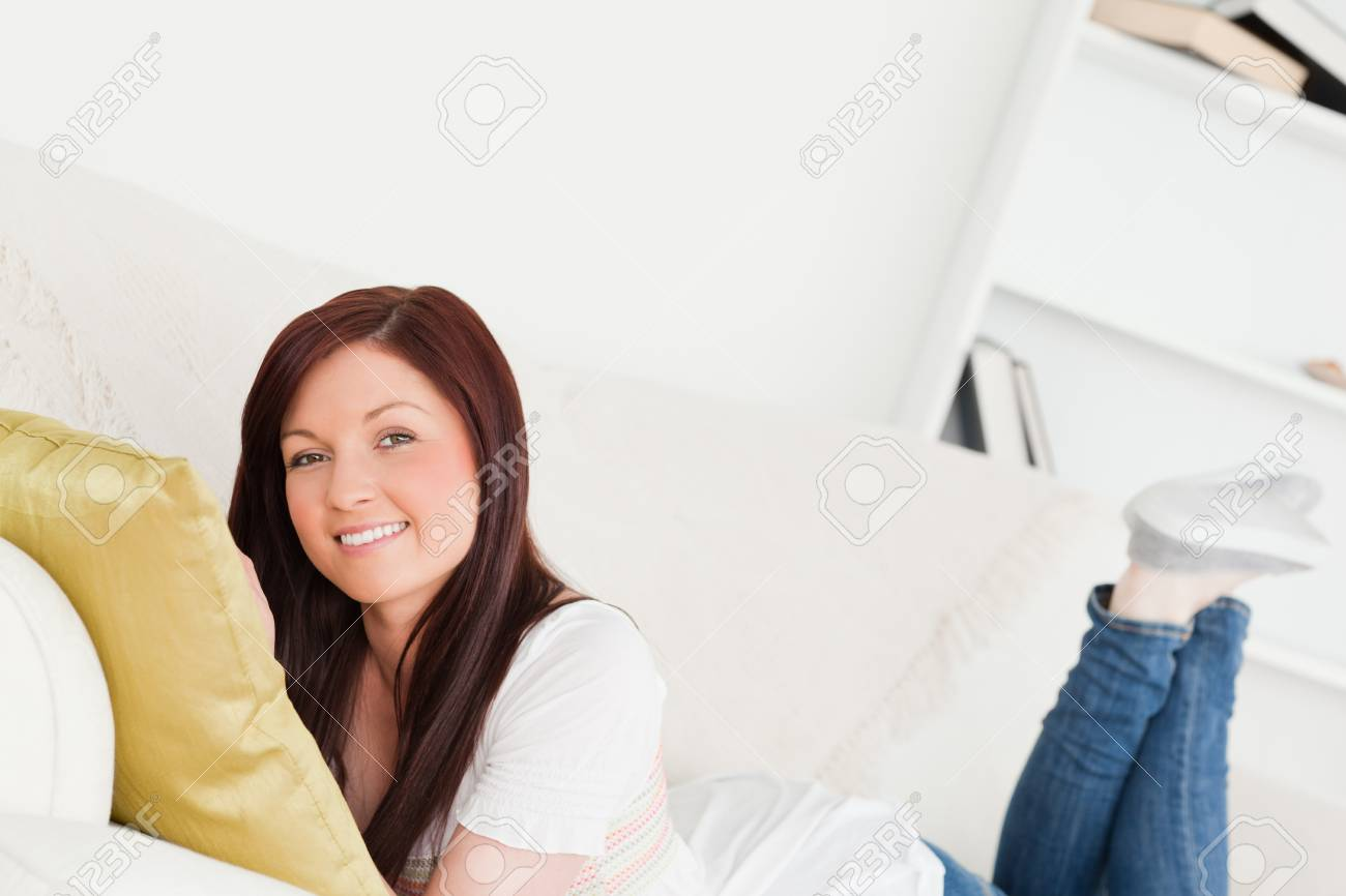 Good looking red-haired woman posing while lying on a sofa in the living room Stock Photo - 10068799