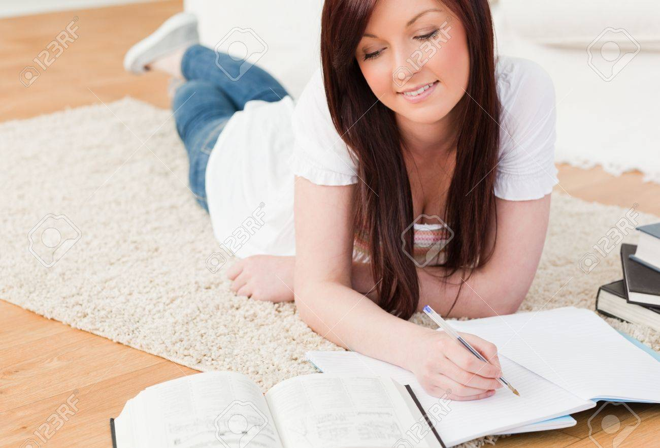 Beautiful red-haired girl studying for while lying on a carpet in the living room Stock Photo - 10069521