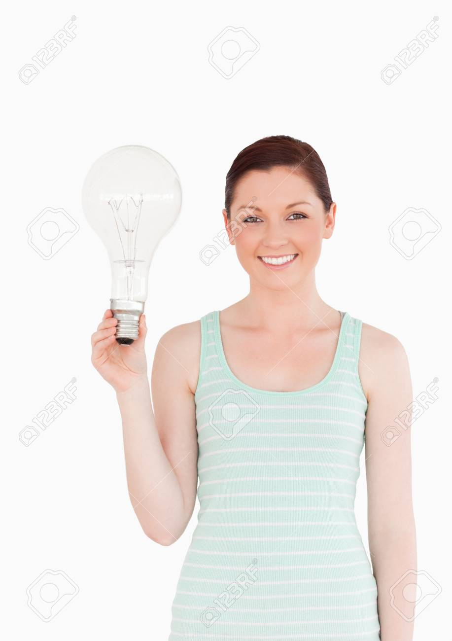 Gorgeous red-haired female holding a bulb while standing on a white background Stock Photo - 10069634