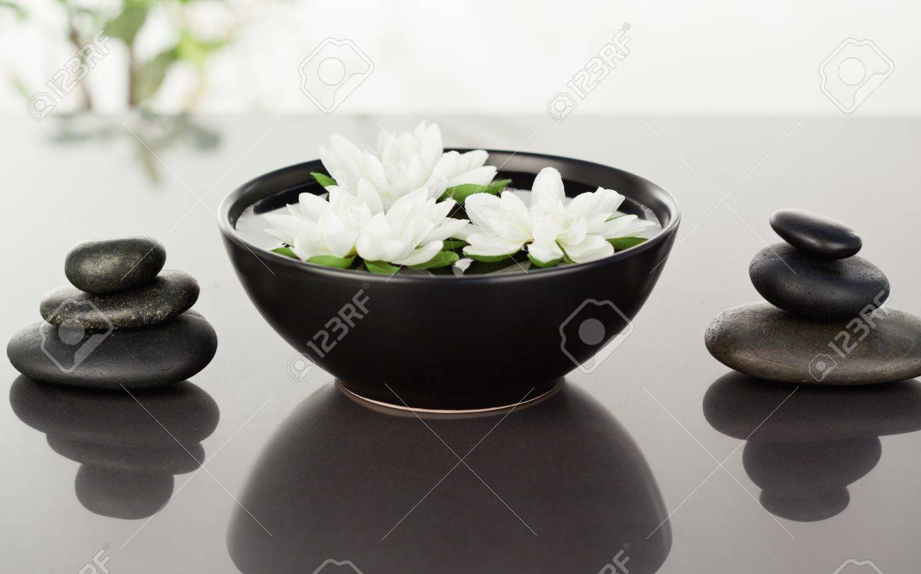 Flowers floating surrounded by stacks of black pebbles Stock Photo - 10074504