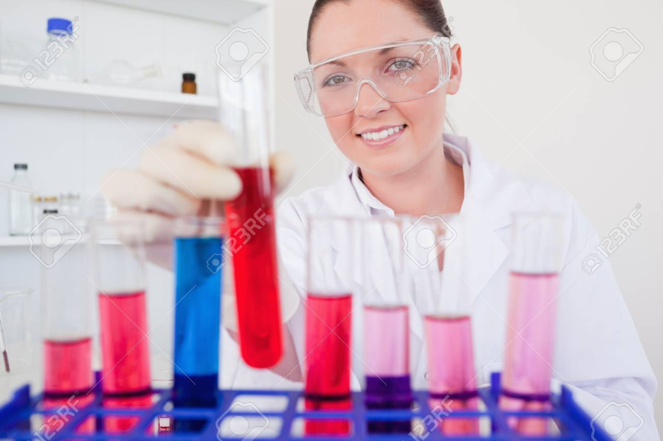 Gorgeous red-haired female holding a test tube in a lab Stock Photo - 10072722