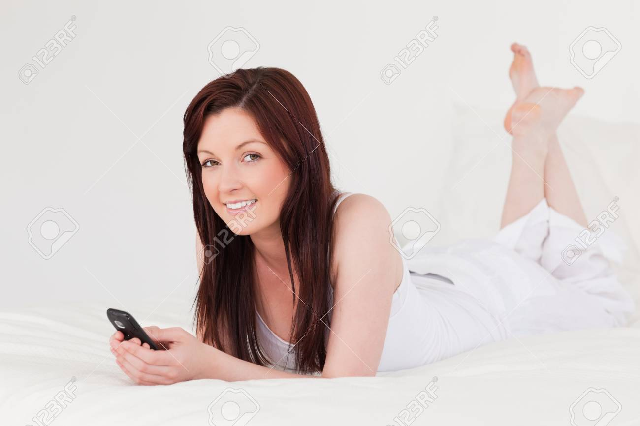 Attractive red-haired female writing a text on her mobile while lying on her bed Stock Photo - 10070774