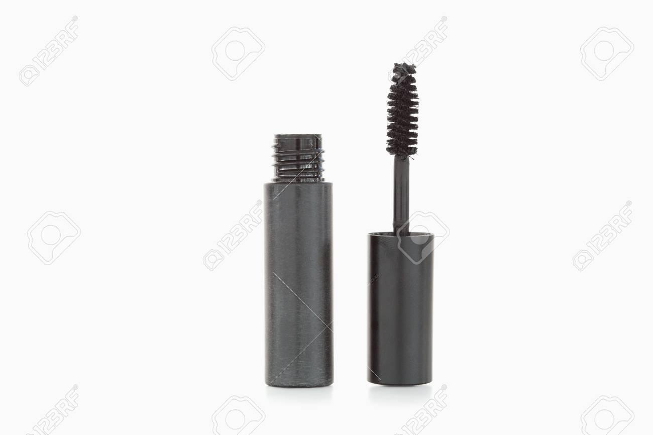 A black mascara brush and tube against a white background Stock Photo - 10069582