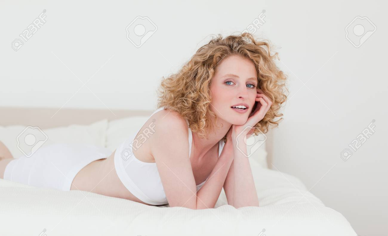 Good looking blonde woman relaxing while lying on her bed in her appartment Stock Photo - 10069730