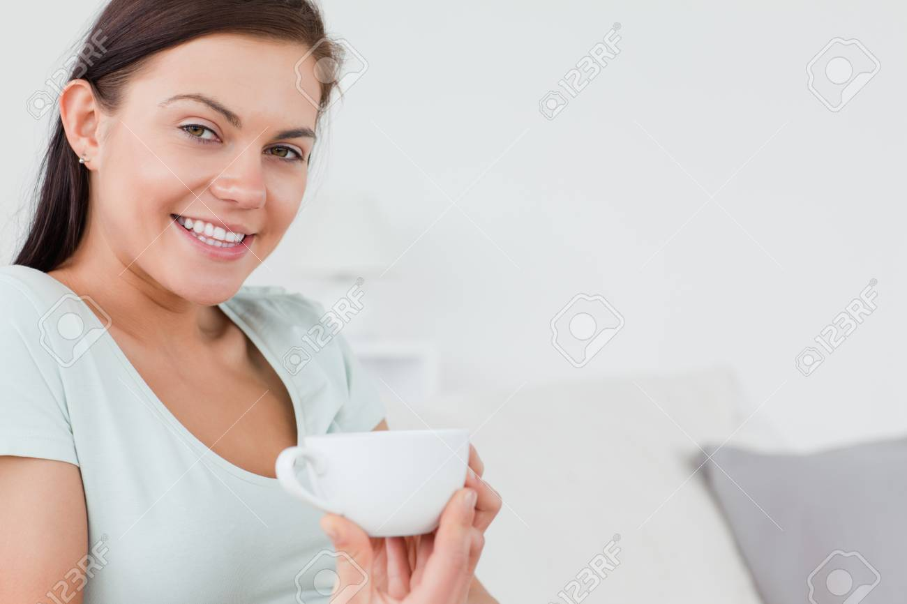 Close up of a brunette sitting on a sofa with  a cup of coffee looking at the camera Stock Photo - 10071829