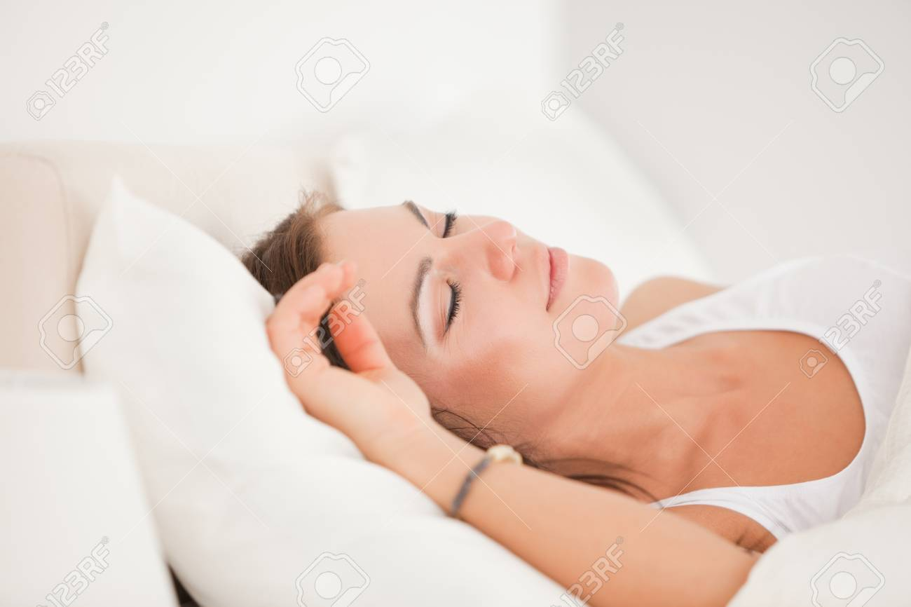 Brunette sleeping in her bed against a white background Stock Photo - 10070101