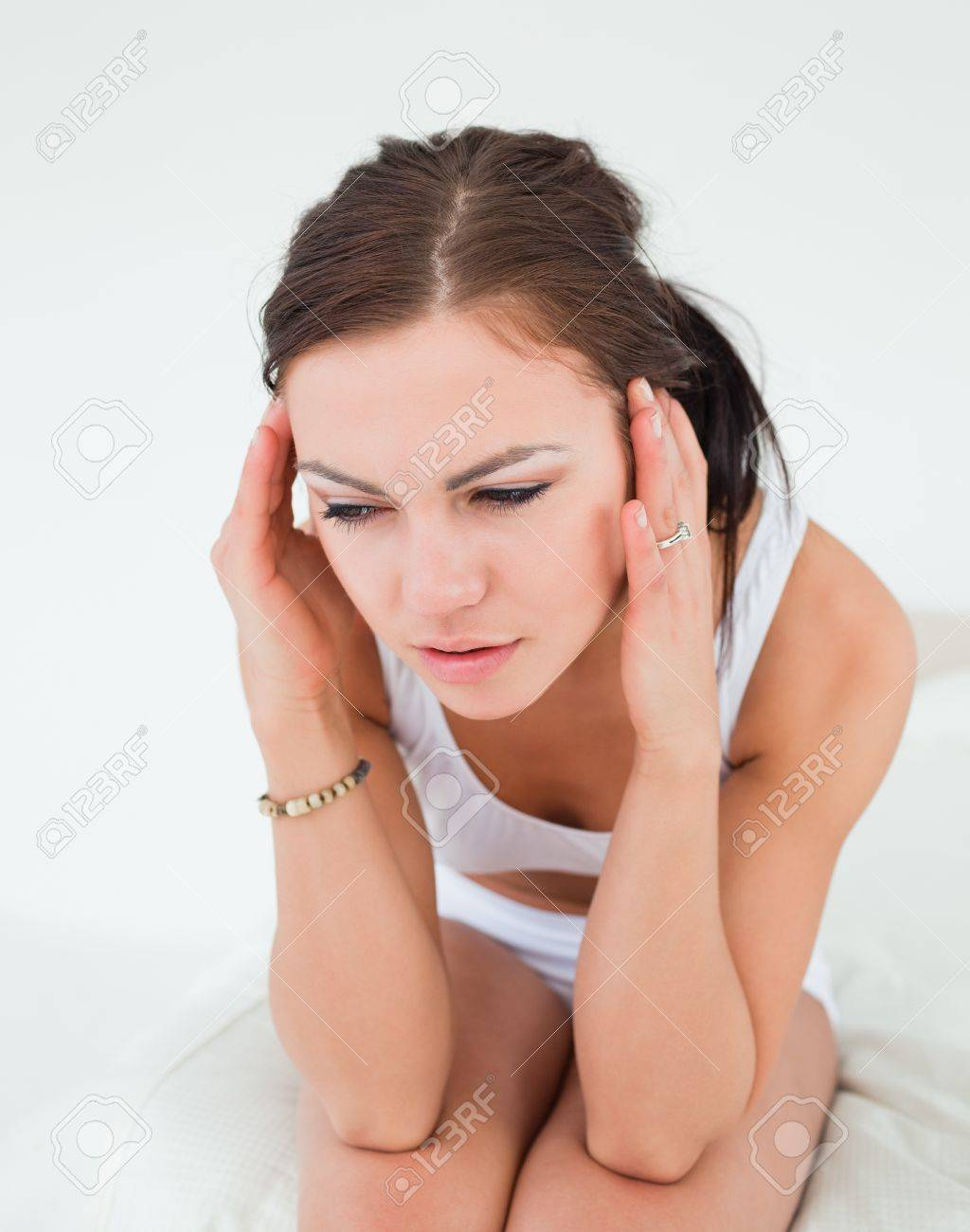 Cute brunette having a headache against a white background Stock Photo - 10071428