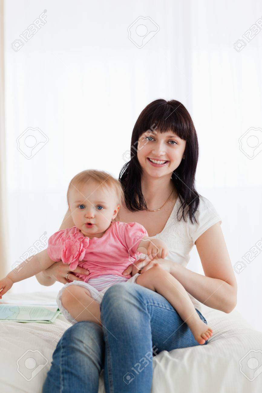 Attractive brunette woman holding her baby on her knees while sitting on a bed in her appartment Stock Photo - 10072261