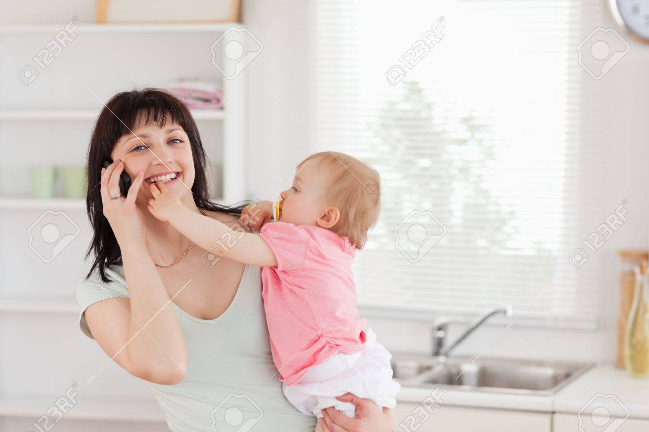 Lovely woman on the phone while holding her baby in her arms in the kitchen Stock Photo - 10070341